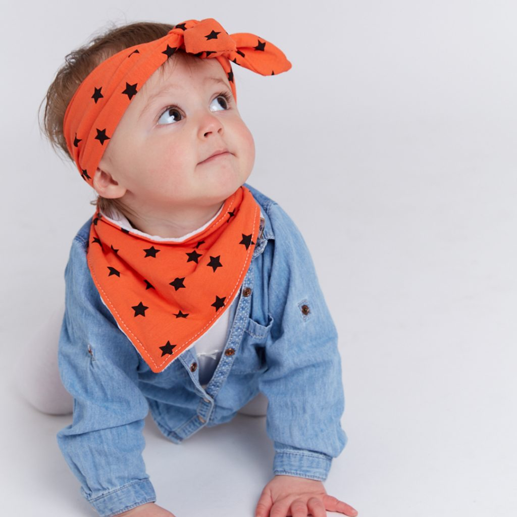 Boy wearing orange star Frankie Lola bib and head wrap